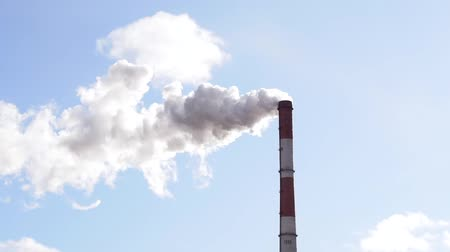 дымоход : smoke from the factory chimney against the blue sky. The concept of environmental pollution