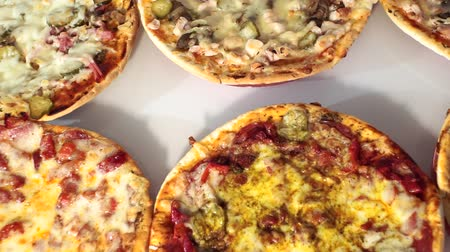 kiełbasa : pizza on white background, six different types of pizza. With mushrooms, with sausage, with ham, with cheese.