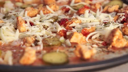 close cropped : Cooking pizza, sprinkle pizza with cheese, close-up, selective focus.