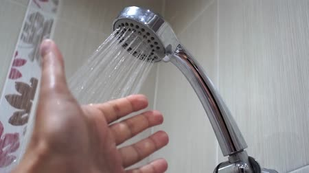 suporte : water flowing from shower head. a mans hand checks the water, hot, cold. Concept of hygiene and save water