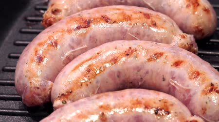 kiełbasa : grilled sausages on a grill pan close-up. The preparation of sausages, pork kupaty