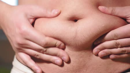 young caucasian man grabbing the fat of his hairy stomach. belly fat, weight loss, overweight