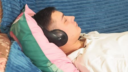 выражающий : young man is resting on the sofa with headphones close-up at home listening to relaxing music, calm music. relaxation, peace of mind. headphones and listening to music Стоковые видеозаписи