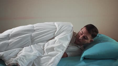 young man goes to bed, falls asleep in a comfortable bed. Sleeping man Stock mozgókép