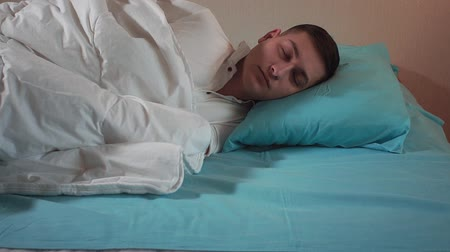 Young guy getting ready to sleep on the bed close-up. Healthy sleep