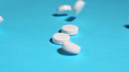 white pills on a blue background close up Wideo