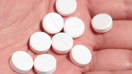 aszpirin : white round pills in a mans hand close-up. medical concept Stock mozgókép