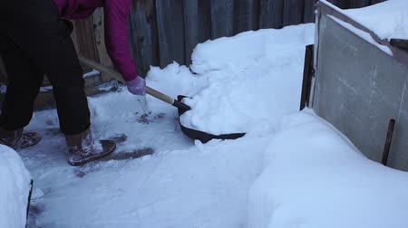 srážky : snow removal with a shovel. a woman cleans a path with a shovel from the fallen snow