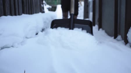 snow removal : woman shoveling snow from a walkway. close up. snow shoveling at home. winter season