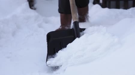 Łopata : Low short of a man shoveling snow from a walkway. close-up selective focus. snow shoveling at home Wideo