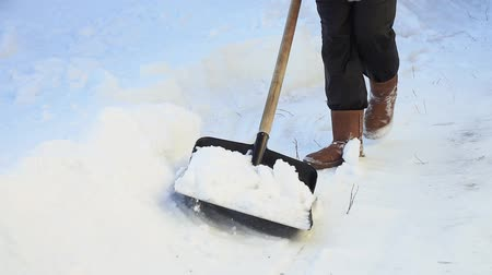 Łopata : woman shoveling snow from a walkway. close up. snow shoveling at home. winter season