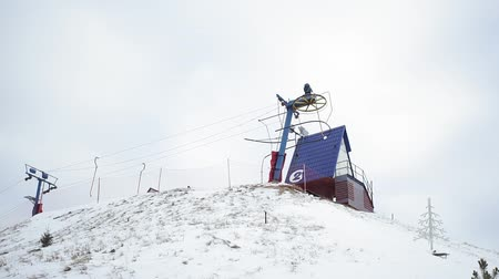 narciarz : Ski resort and on ski T-bar lift on slope, handheld. Town under snow, skiers using surface lift at winter. Climbing to hill using ski-lift. Winter