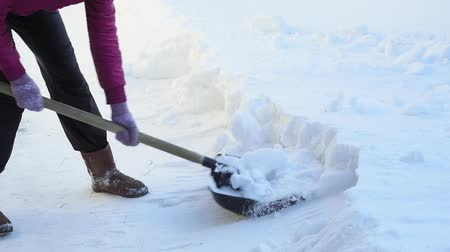 snow removal : cleans snow with a shovel. woman cleans snow in the snow with a shovel.