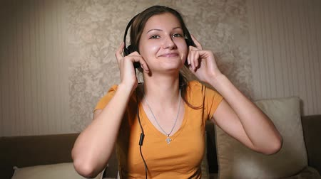 listening music : teenage girl in headphones, gesturing and moving head. Young pretty teenager listening to music at home. Leisure, resting, lifestyle