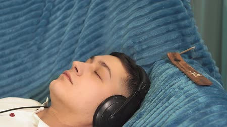 listening music : young man milinal listening to relaxing music, lying on the couch. pleasant music, relaxation Stock Footage