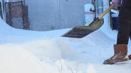 Łopata : snow removal with a shovel. a woman cleans a path with a shovel from the fallen snow