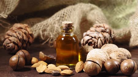 orzech : cosmetic oil and nuts on an old wooden background, selective focus