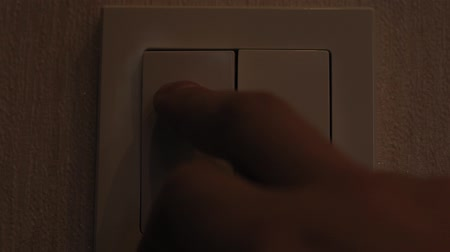 hasznosság : Mans Hand Turning Light Switch In Double Switch. turning on the light
