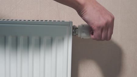 mounted : rotating white temperature valve with hand on wall mounted heating water radiator Stock Footage