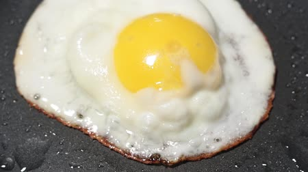 tojás : fried egg close-up. Breakfast food preparation of 1 chicken egg in frying pan