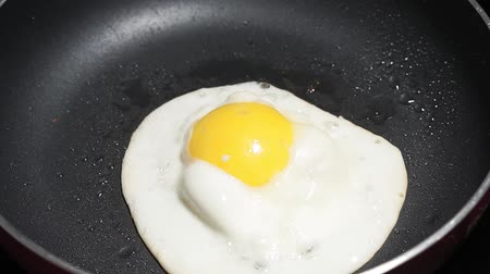 eszik : Fried Egg in Frying Pan With Hot Oil on Kitchen Cooker. close-up Stock mozgókép