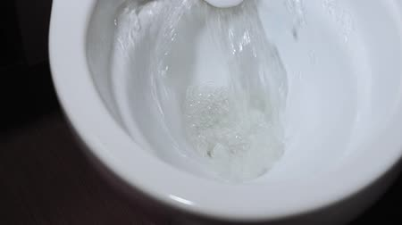 banheiro : flushes the water in the toilet. Close-up view of water running down the toilet in the bathroom Vídeos