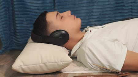 listening music : young man listens to quiet music with headphones. relaxation Stock Footage