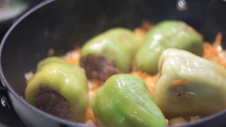 стручковый перец : stuffed peppers in a saucepan in tomato sauce closeup. concept of healthy eating.