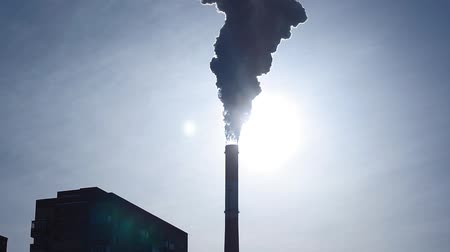damp : Smoke pollution from smokestacks over residential buildings city skyline silhouette.