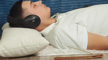 listening music : man lying on the bed listens to music headphones and relaxes. Concept of music, relaxation, dream Stock Footage