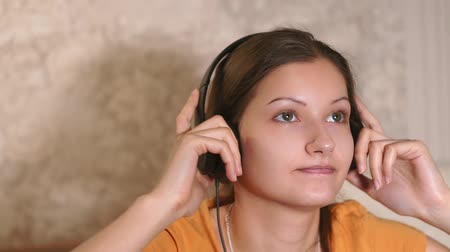 listening music : young girl close-up listening to music with headphones, at home. Stock Footage