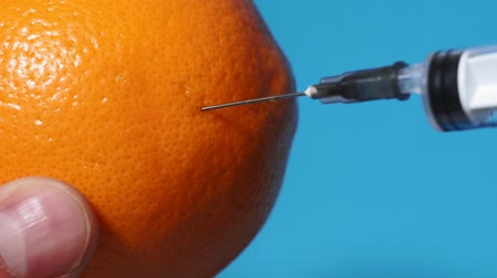 seringa : Injection into grapefruit - fruit and syringe chemical GMOfood on a blue background Stock Footage