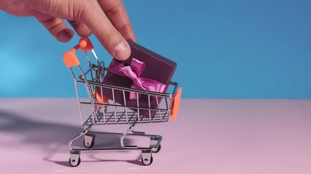 miniatűr : gifts in a shopping cart on a blue pink background. Abstract design element, annual sale, shopping season concept. Stock mozgókép