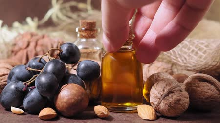 material body : bottle of aroma oil, nuts. Set of organic cosmetic products, selective focus. Spa, massage, female treatment, aromatherapy, body care, authentic raw material