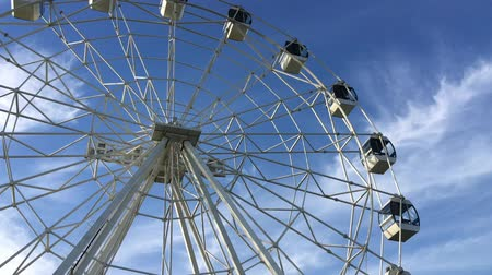 palce : A white Ferris wheel is spinning