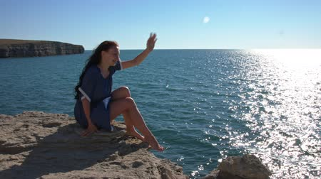 созерцать : Girl is sitting on the edge of the cliff and looks at the ocean