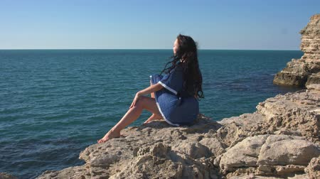 созерцать : The girl in the blue dress sitting by the sea. A strong wind