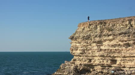 созерцать : The figure of a woman at the very edge of the cliff