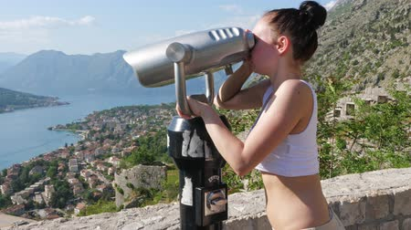 magasság : A girl with binoculars watching the city and the bay Stock mozgókép