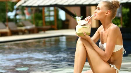 Beautiful girl sitting at the edge of swimming pool and drinking from coconut