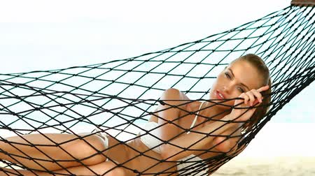 гамак : Smiling woman relaxing in a hammock on a sandy beach enjoying an idyllic tropical getaway Стоковые видеозаписи