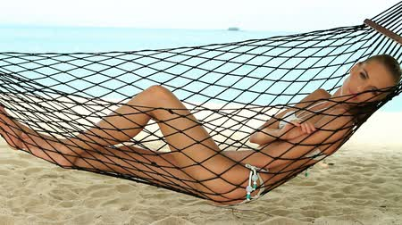 гамак : Beautiful woman full of vitality reclining suntanning in a hammock on a tropical beach