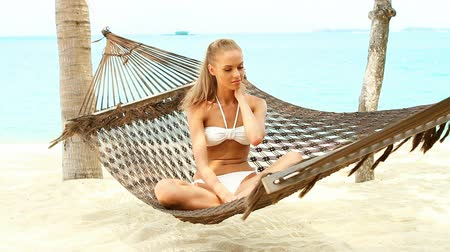 гамак : Beautiful smiling woman with long blonde hair sitting cross legged in a hammock at the beach looking to the side off camera Стоковые видеозаписи
