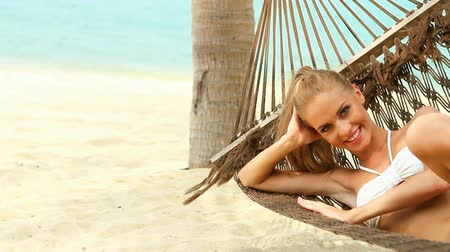 гамак : Attractive woman reclining in a hammock strung from a palm enjoying the tranquillity of a tropical beach