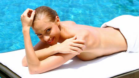 opalenizna : Young woman relaxing close to swimming pool in summertime