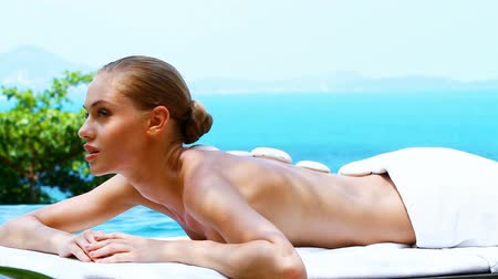 massages : Relaxed woman resting on bed close to swimming pool