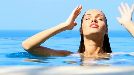 model : Charming woman reposing in exotic swimming pool Stock Footage