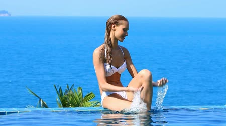 yüzme havuzu : Woman sitting at the edge of infinity swimming pool Stok Video