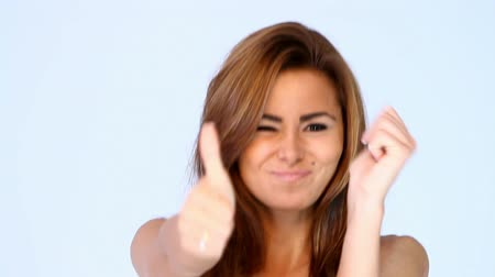 izgatott : Smiling young woman showing thumbs up for success