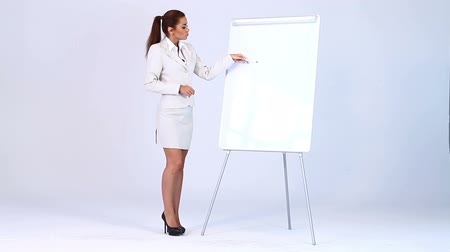 стоять : Cute business woman showing points at flipchart Стоковые видеозаписи